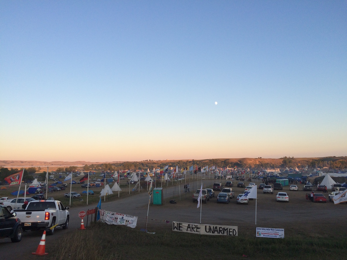 """""""We Are Unarmed"""" banner at the mouth of Oceti Sakowin/Red Warrior Camp (Photo: Nadya Tannous)"""